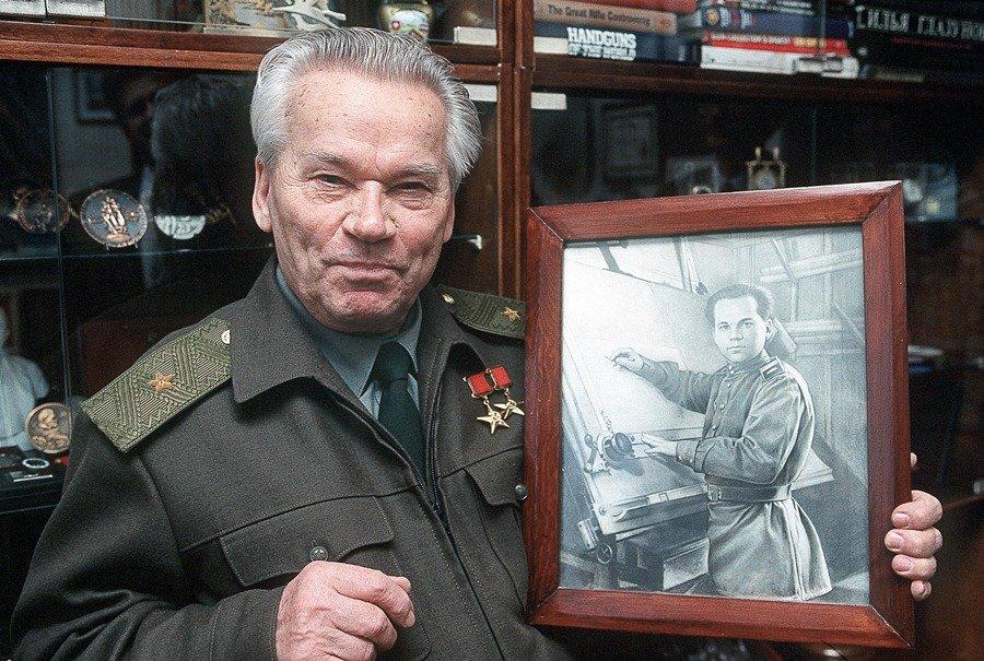 Прославленный конструктор стрелкового оружия, создатель автоматов семейства АК Михаил Калашников со своей фотографией тех лет, когда он конструировал свой автомат.