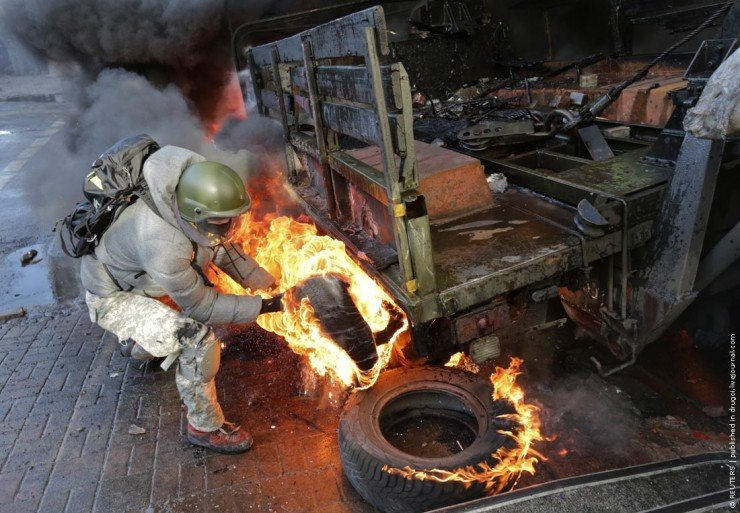 A protester pulls a burning tyre during clashes with police in Kiev