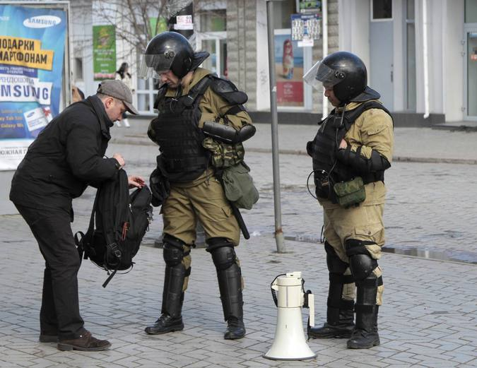 Members of Crimean self-defence unit spot check man's bag a street in Simferopol