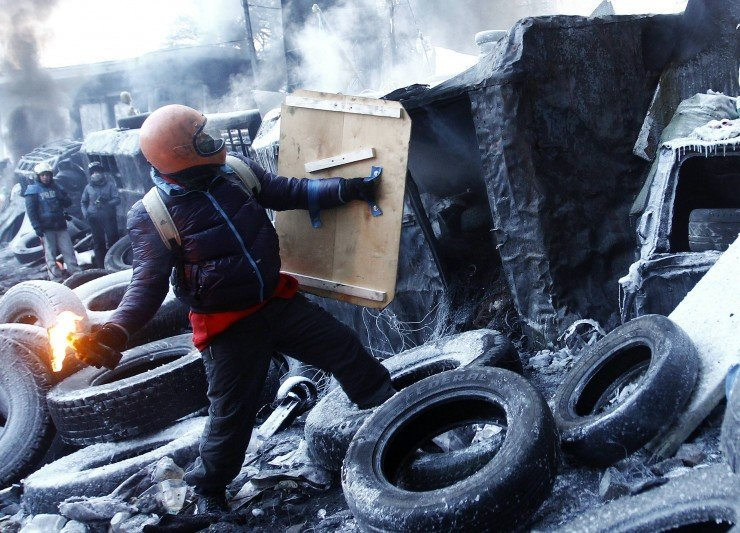 An anti-government protester holds a Molotov cocktail at a barricade at the site of clashes with riot police in Kiev