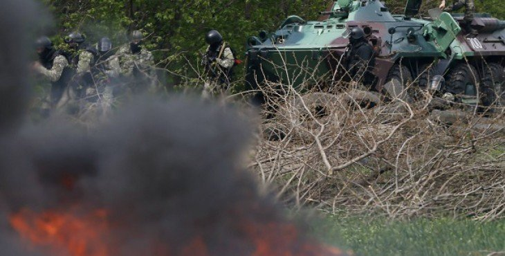 Ukrainian security force officers are deployed at a checkpoint set on fire and left by pro-Russian separatists near Slaviansk