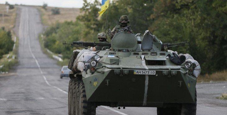 Ukrainian servicemen ride in an armoured vehicle near Debaltseve