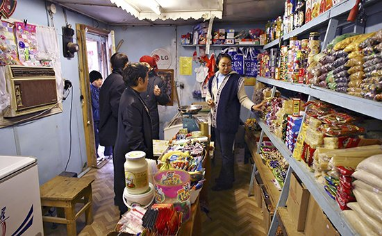 Indira Koshkarbayeva, right, helps customers in her store in