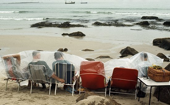 People. Holidays. England. pic: 1970. Hardy holidaymakers hoping for a picnic have to endure the British climate as they take shelter on the beach by covering themselves in a plastic sheet.