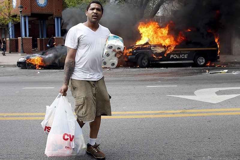 A man with goods looted from a store walks past burning vehicles during clashes in Baltimore, Maryland