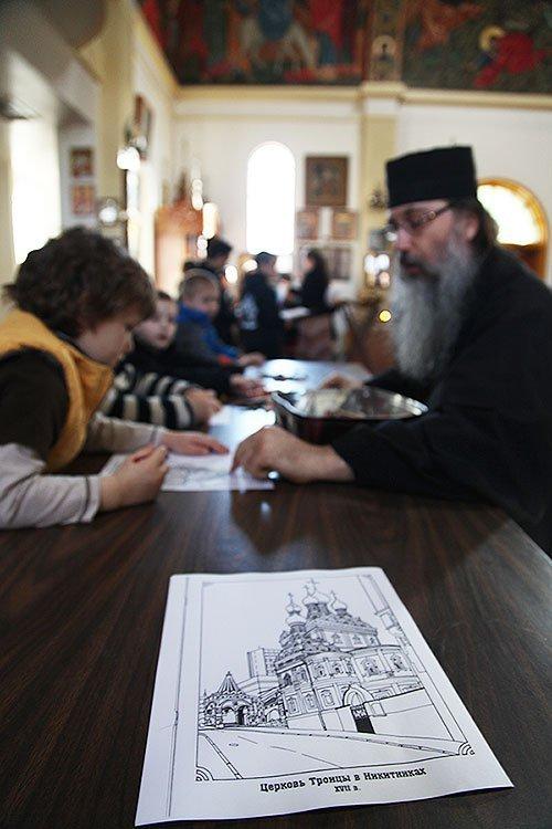 Самым маленьким батюшка помогает раскрашивать раскраску с изображением храмов в России.