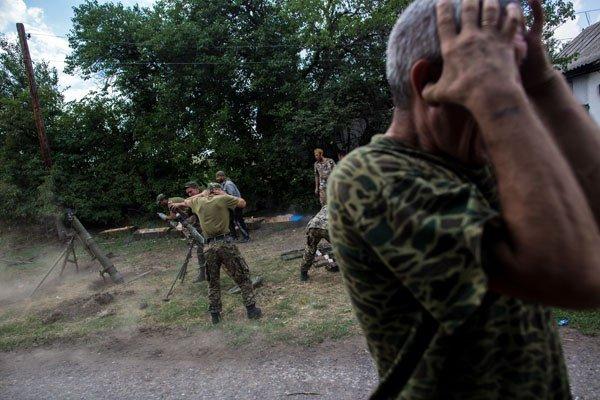 Бойцы ополчения ведут огонь из минометов во время боя за пограничный населенный пункт Кожевня под Снежным.