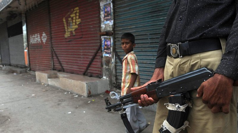 A Pakistani boy walks past a policeman on duty in a troubled area of Karachi on August 13, 2011. The independent Human Rights Commission of Pakistan says 800 people, most of them poor, have died since January, including 300 last month alone.  AFP PHOTO/Rizwan TABASSUM