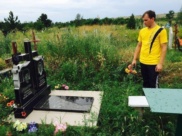 © РИА Новости Денис Судаков на могиле своих родителей, погибших в тот же день, что и Стенин