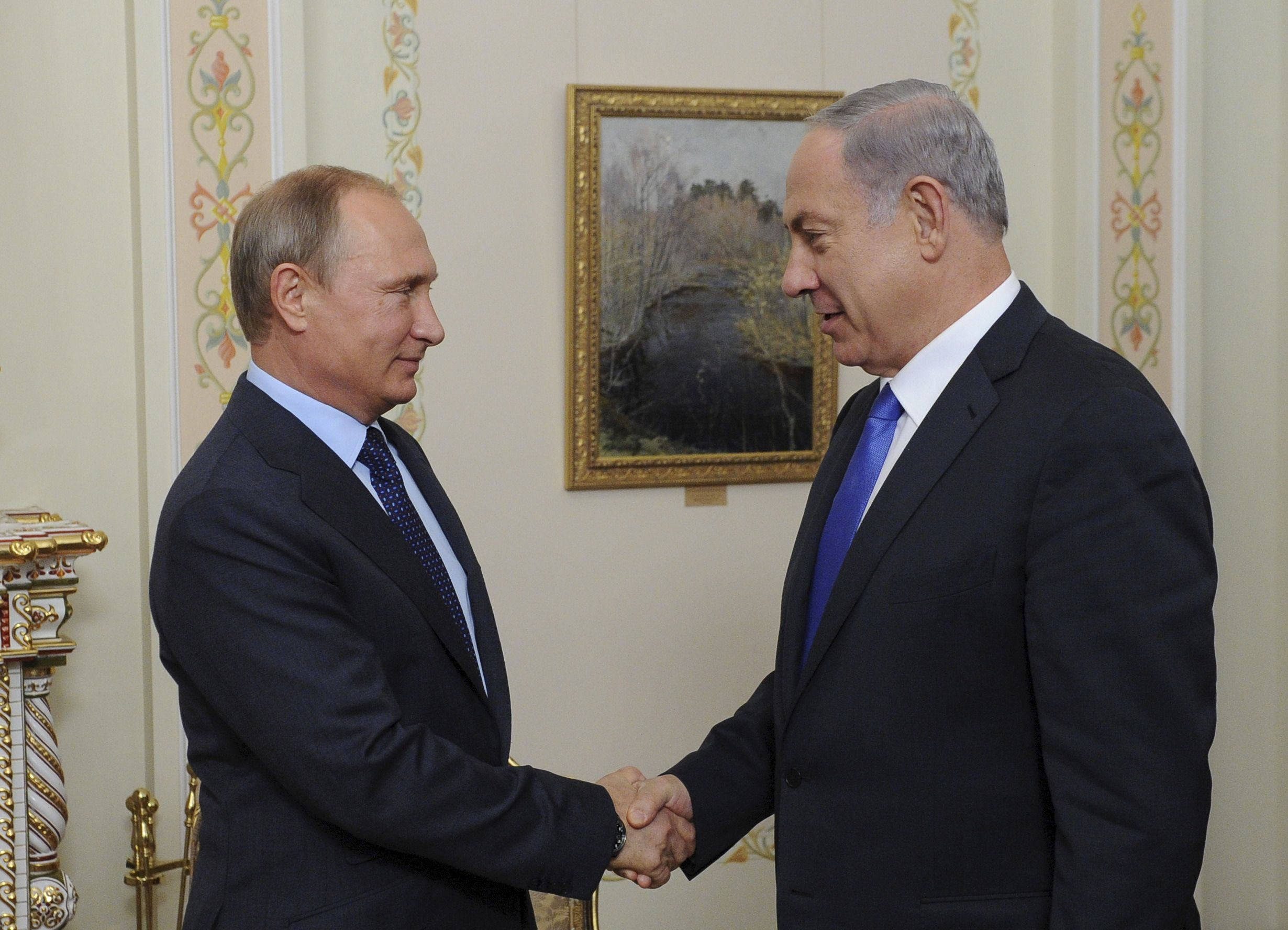 Russian President Vladimir Putin (L) and Israeli Prime Minister Benjamin Netanyahu shake hands during their meeting at the Novo-Ogaryovo state residence outside Moscow, Russia, September 21, 2015. Netanyahu said his visit to Moscow on Monday was aimed at preventing clashes between Russian and Israeli military forces in the Middle East. REUTERS/Mikhail Klimentyev/RIA Novosti/Pool ATTENTION EDITORS - THIS IMAGE HAS BEEN SUPPLIED BY A THIRD PARTY. IT IS DISTRIBUTED, EXACTLY AS RECEIVED BY REUTERS, AS A SERVICE TO CLIENTS. - RTS24WH