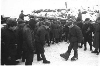 """На фото: Советский солдат под Сталинградом показывает немецкие """"караульные боты""""."""